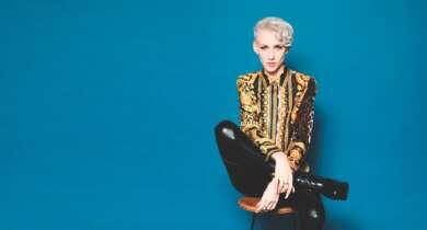 Lisa Eckhart sitzt vor einem blauen Hintergrund