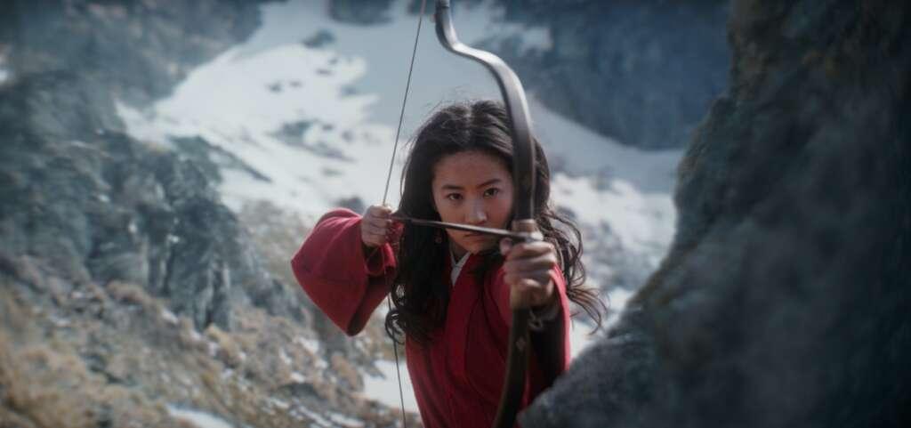 Filmszene aus Mulan: Die Kriegerin Mulan steht mit ihrem Schwert vor einer Berglandschaft.