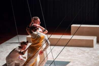 """Drei Tänzer*innen stehen für das Stück """"Unmute"""" auf der minimalistisch gestalteten Bühne des FFT Düsseldorf."""