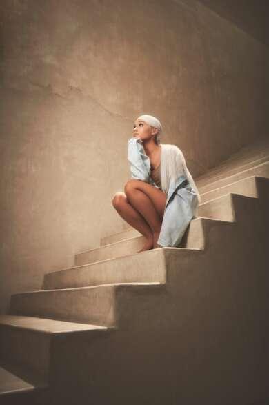 Ariana Grande in der Hocke auf einer Treppe