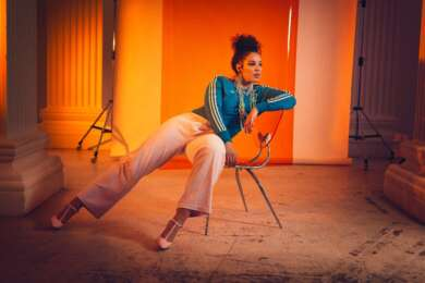 Die Hamburger Sängerin Binta auf einem Stuhl vor einem orangen Hintergrund