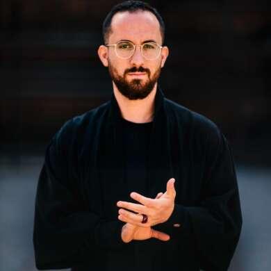 Igor Levit mit gefalteten Händen und Brille vor einem schwarzen Hintergrund
