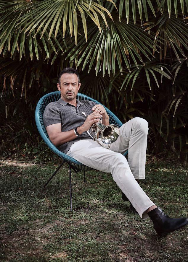 Till Brönner sitzt mit seiner Trompete in den Händen auf einem Stuhl. Im Hintergrund sind Palmen zu sehen.
