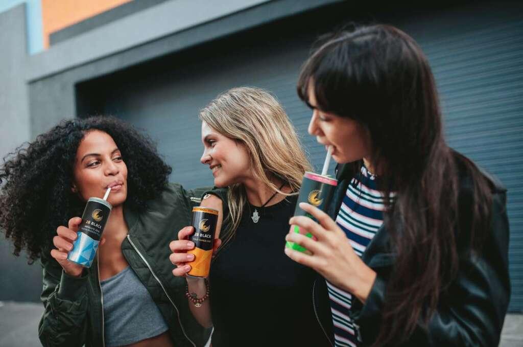 Drei Frauen stehen mit verschiedenen Sorten von 28 BLACK in der Hand auf vor einem grauen Gebäude