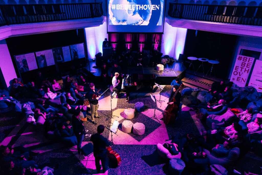 Eine Gruppe von Musiker*innen steht in einem violett ausgeleuchteten Raum und spielt für ein Publikum, das am Rand sitzt. Konzert im Rahmen von BeBeethoven, eine Themenwoche zum 250. Geburtstag von Ludwig van Beethoven.