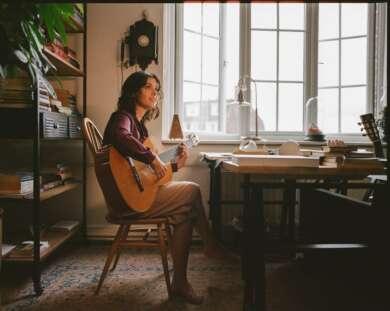 Katie Melua am Schreibtisch mit Gitarre