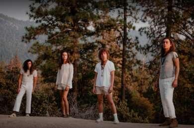 Die Bandmitglieder von Greta van Fleet stehen in weiß gekleidet vor einigen Tannenbäumen.