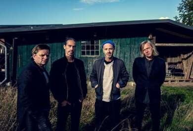 Die vier Bandmitglieder von Selig stehen mit Händen in den Taschen vor einem blau gestrichenen Schuppen.