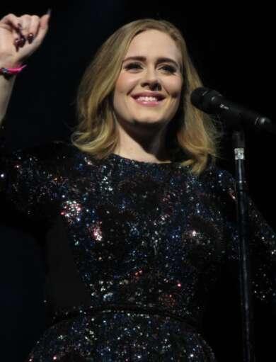 Adele steht mit einem funkelnden Kleid vor einem Mikrofon und hebt den linken Arm.