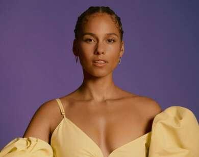 Alicia Keys steht in einem gelben Oberteil vor einem violetten Hintergrund. Das Bild zeigt die Künstlerin von der Körpermitte aufwärts.