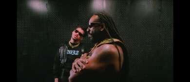 Bad Bunny steht mit Booker T in einem dunklen Raum. Beide Tragen Sonnenbrillen, Booker T starrt mit verschränkten Armen nach vorne, während Bad Bunny in die Kamera guckt.