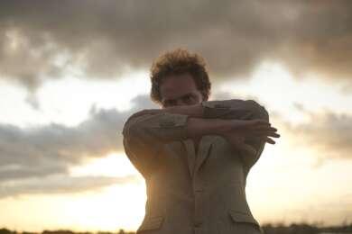 Karwendel steht mit verschränkten Armen vor dem Gesicht vor einer Wolkenfront. Im Hintergrund geht die Sonne unter.