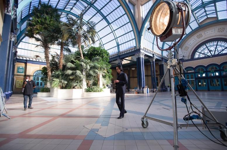 Nick Cave spaziert in einer großem Halle umher, die mit einem Glasgewölbe ausgestattet ist.