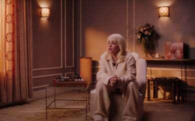 """Billie Eilish im Vevo-Interview zu """"Happier than ever"""". Die Künstlerin sitzt in einem Sessel neben einem Plattenspieler."""
