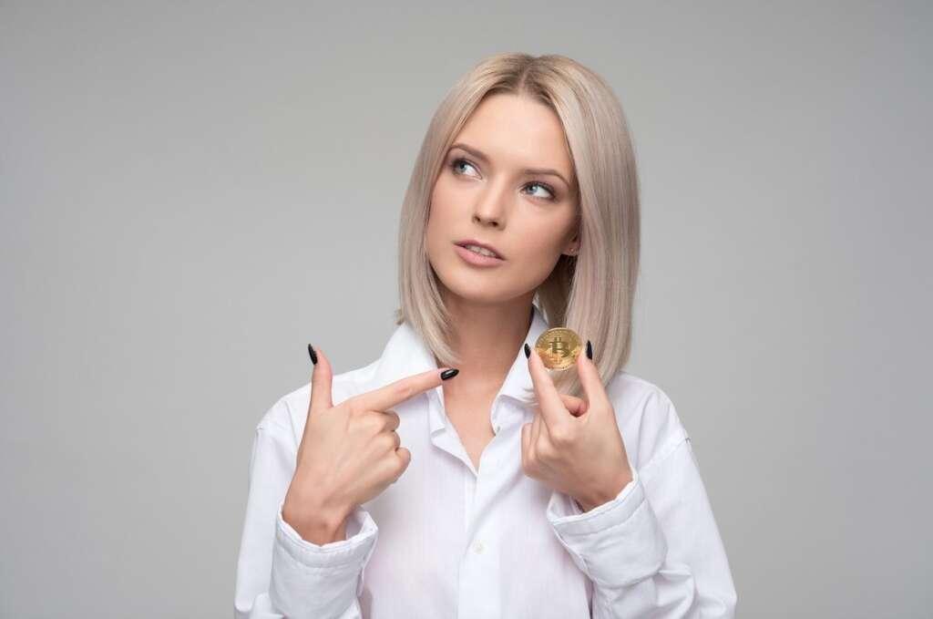 Frau zeigt auf Bitcoin in ihrer Hand