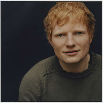 Ed Sheeran grüner Pullover schwarzer Hintergrund