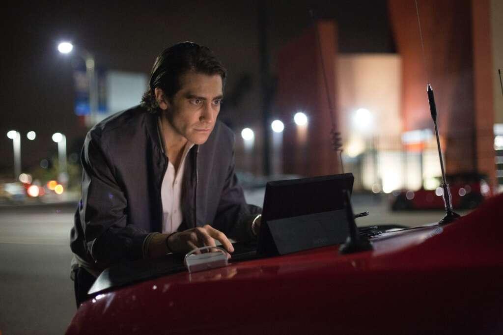 Szenenbild aus Nightcrawler: Lou Bloom (Jake Gyllenhaal) tippt auf einen Laptop auf der Kühlerhaube eines roten Autos, im Hintergrund das nächtliche LA.