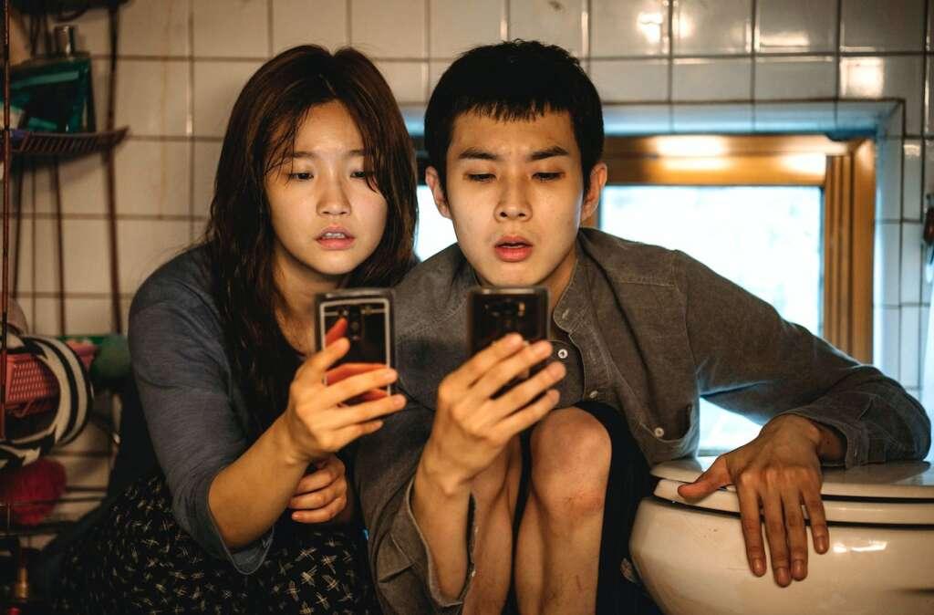 Szenenbild aus Parasite: Ki Jung (Park So-dam) und Ki Woo (Choi Woo-shik) knien mit dem Smartphone in der Hand neben der Toilette.