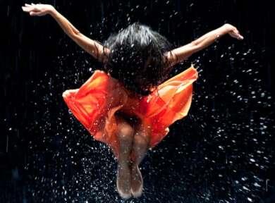 Eine Tänzerin in orangenem Kleid mit ausgebreiteten Armen vor schwarzem Hintergrund mit Wassertropfen.