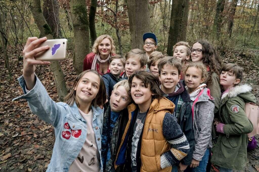 """Szenenbild aus """"Rufmord"""": Eine Gruppe Schüler:innen und eine Lehrerin lächeln für einen Selfie in die Handykamera. Im Hintergrund der Wald."""