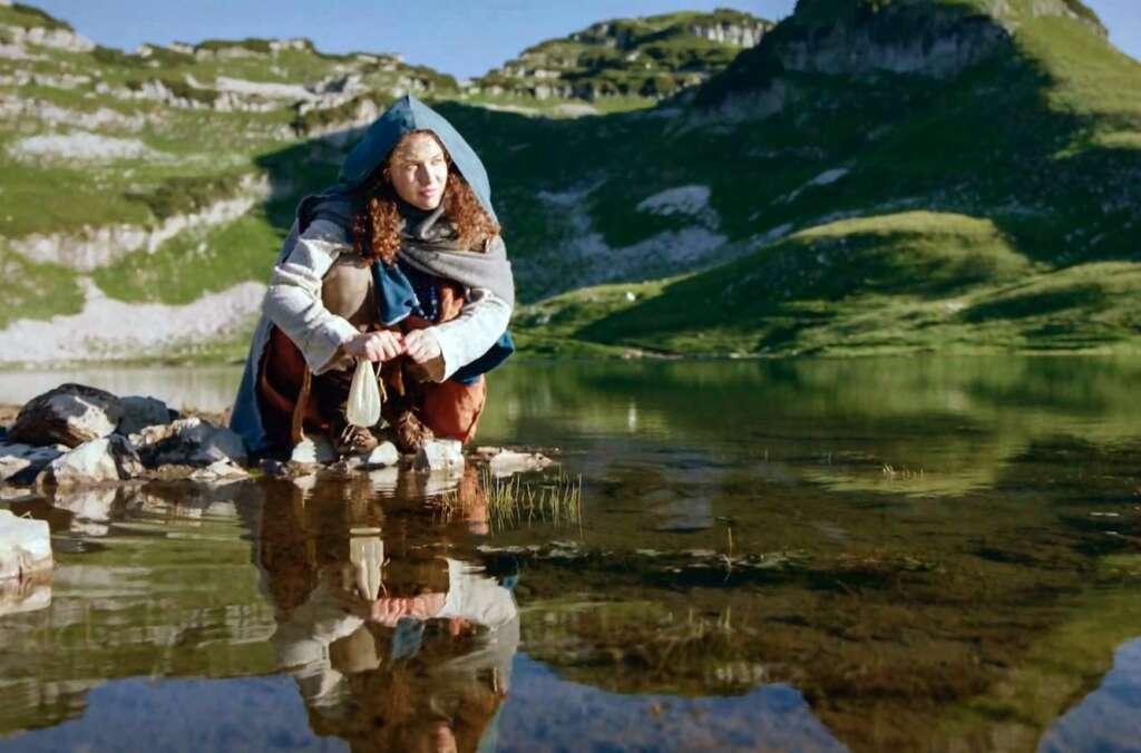 Die Salzfürstin Szenebild: Eine junge Frau in altertümlicher Kluft kniet an einem Bergsee mit einem weißen Beutel in der Hand.