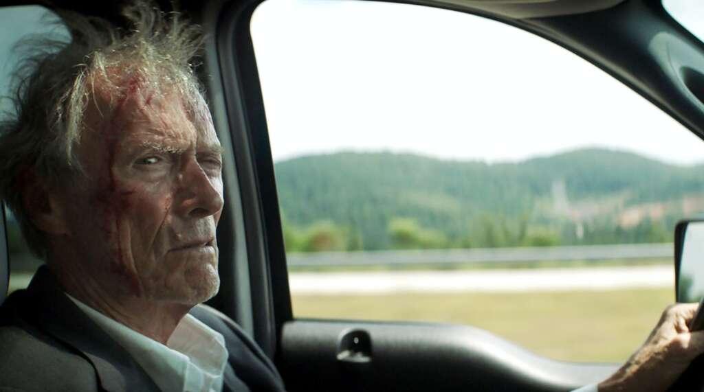 """Szenenbild aus """"The Mule"""": Clint Eastwood sitzt am Steuer eines Autos und starrt grimmig in die Kamera"""