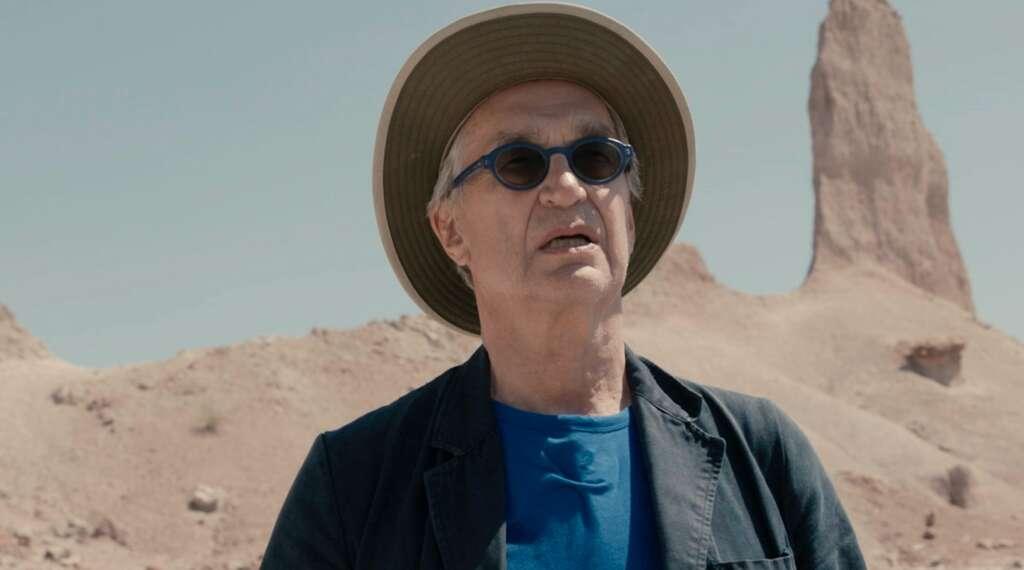 """Wim Wenders während der Dreharbeiten zu """"Desperado"""": Ein Mann mit Hut und blauer Sonnenbrille vor karger Landschaft"""