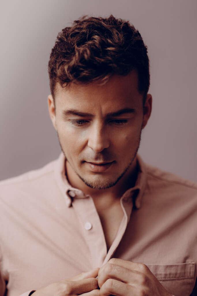 Portrait Alexander Knappe knöpft pinkes Hemd auf