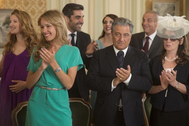 """Szenenbild aus """"Monsieur Claude und seine Töchter"""": Zwei junge, gut angezogene Frauen klatschen lächelnd Beifall, daneben steht ein älteres Ehepaar, ihre Eltern, die mit zweifelndem Gesichtsausdruck applaudieren."""