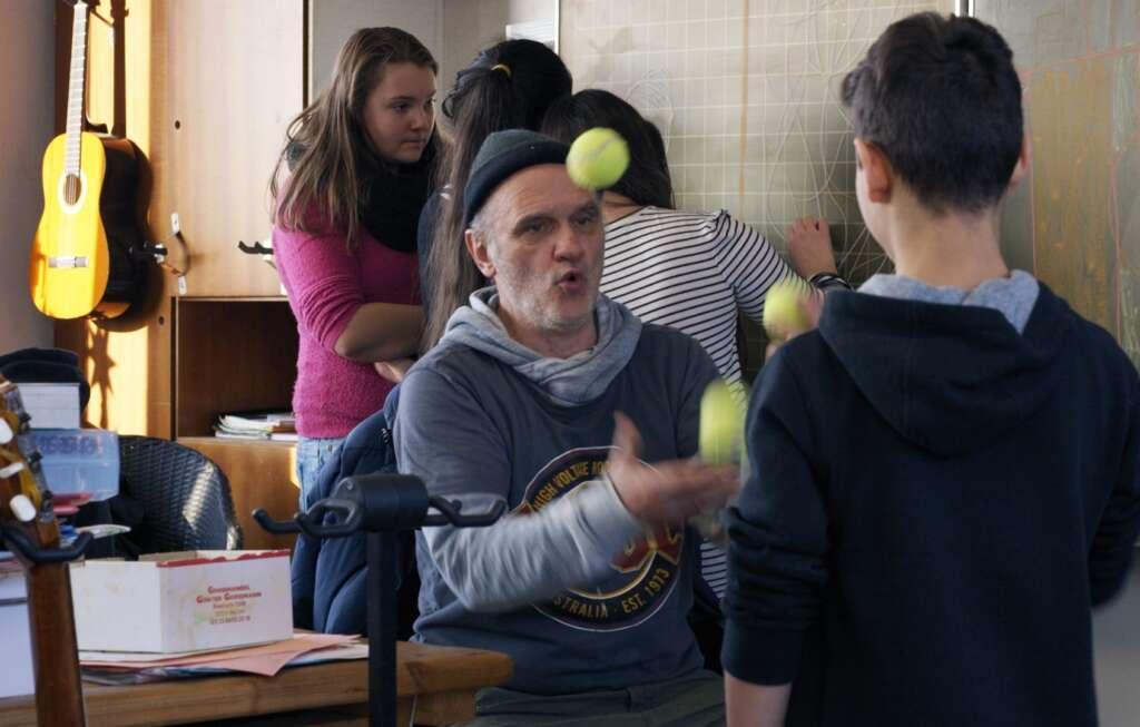 Herr Bachmann jongliert im Klassenzimmer, umgeben von seiner Klasse.