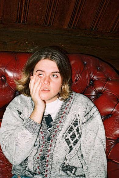 Mann Rote Couch Grauer Sweater Müder Gesichtsausdruck