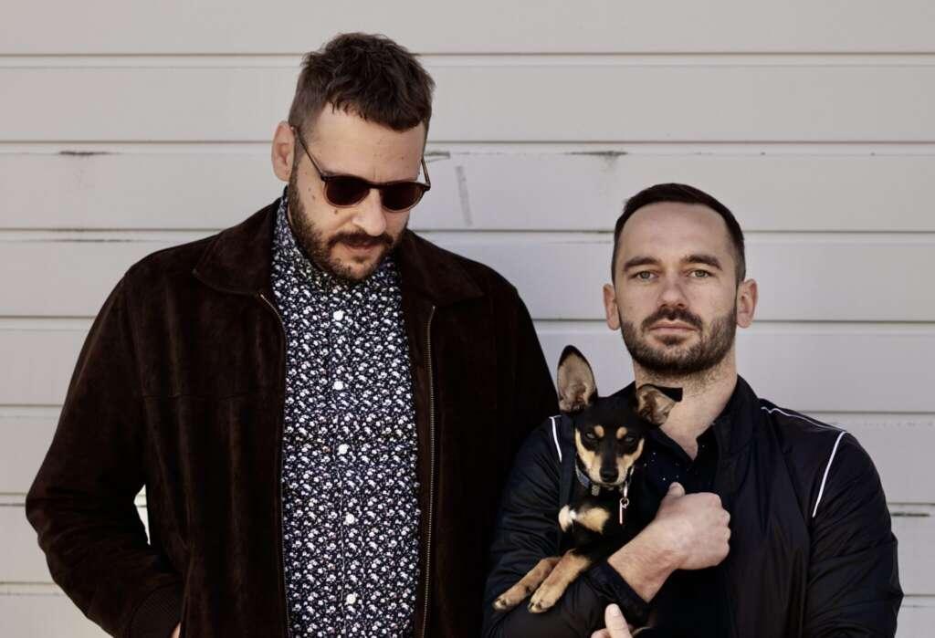 Zwei Maenner mit Hund vor weißen Hintergrund