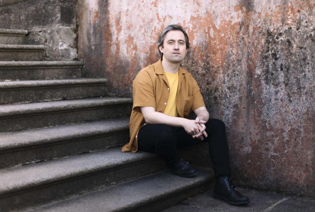 Conor O'Brien sitzend auf Steintreppe, gelbes Shirt, Hemd in Ocker