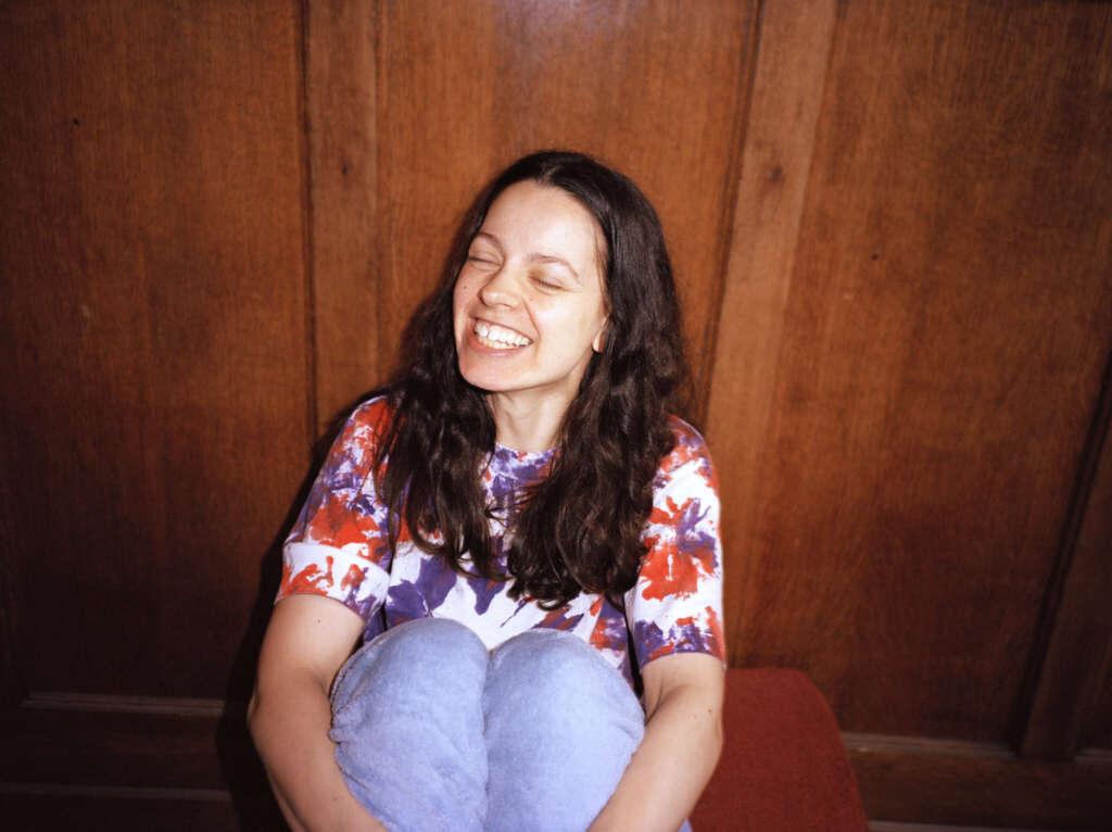 Portrait Tirzah sitzend vor Holzwand