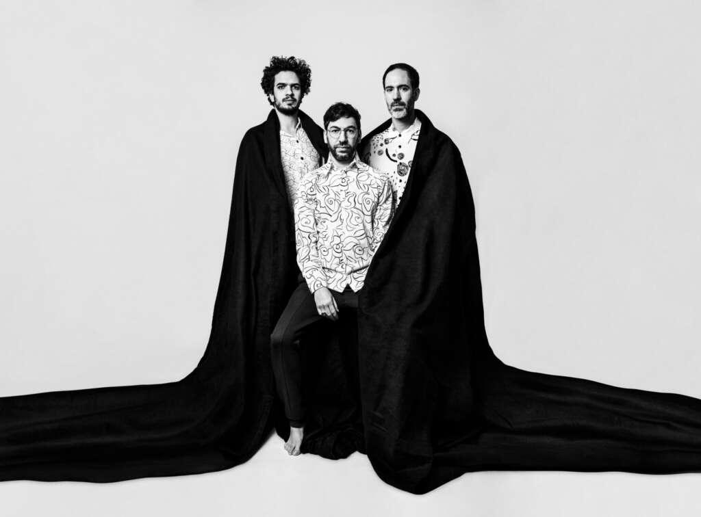 Omer Klein Trio Schwarzer Umhang Weißer Hintergrund