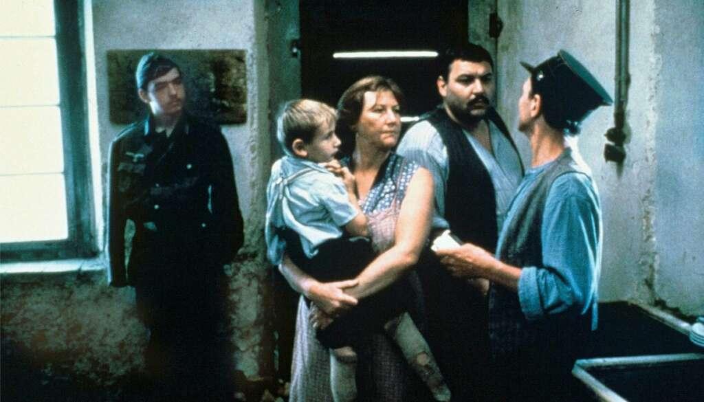 Ein Paar steht vor einem Mann mit Uniformsmütze, die Frau hat einen kleinen Jungen auf dem Arm. Im Hintergrund schaut ein Soldat zu.