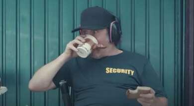 """Ein Mann mit einer Cap und Kopfhörern trinkt Kaffee aus einem Plastikbecher in seiner rechten Hand. In seiner linken hält er ein angebissenes Butterbrot. Er sitzt vor einem Garagentor. Auf seinem T-Shirt steht """"Security""""."""