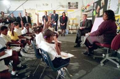 Ein Mann (George W. Bush) sitzt mit einem Buch auf dem Schoß in einem Klassenzimmer. Vor ihm im Halbkreis eine Gruppe Kinder in weißen Hemden. Ein Boom Mic hängt über ihren Köpfen.