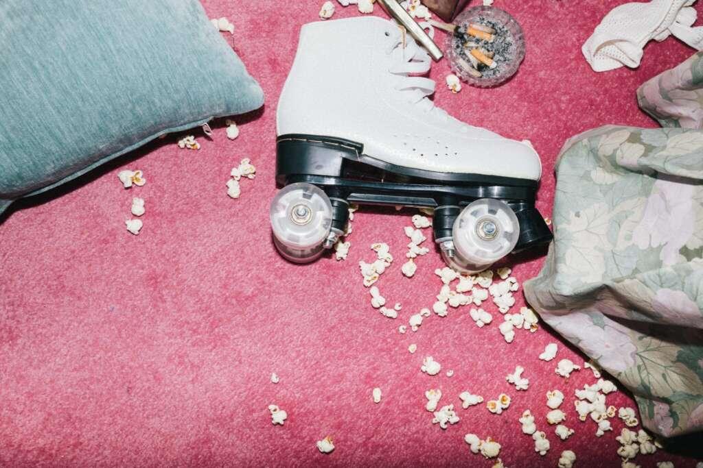 Weißer Rollschuh auf pinkem Teppich, darum liegt Popcorn verstreut.