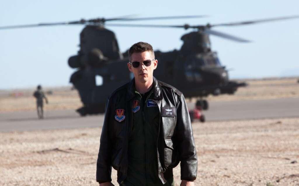 Ein Soldat in schwarzer Lederjacke und Sonnenbrille steht in einer Wüste, im Hintergrund ist ein Militär-Helikopter zu sehen.