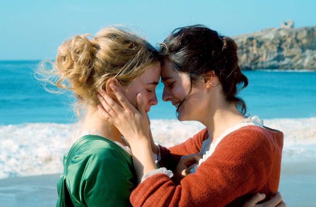 Zwei junge Frauen an einem Strand. Die rechte, in rotem Kleid mit dunklen Haaren, hält das Gesicht der rechten, im grünen Kleid mit blonden Haaren, in den Händen. Beide weinen.