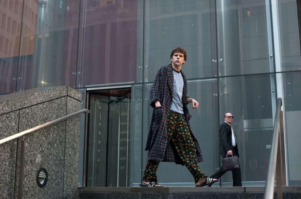 Ein junger Mann, Jesse Eisenberg, steht auf einem Treppenabsatz vor einem Gebäude mit Glasfront. Er trägt Schlafanzug, Bademantel und Flip-Flops.