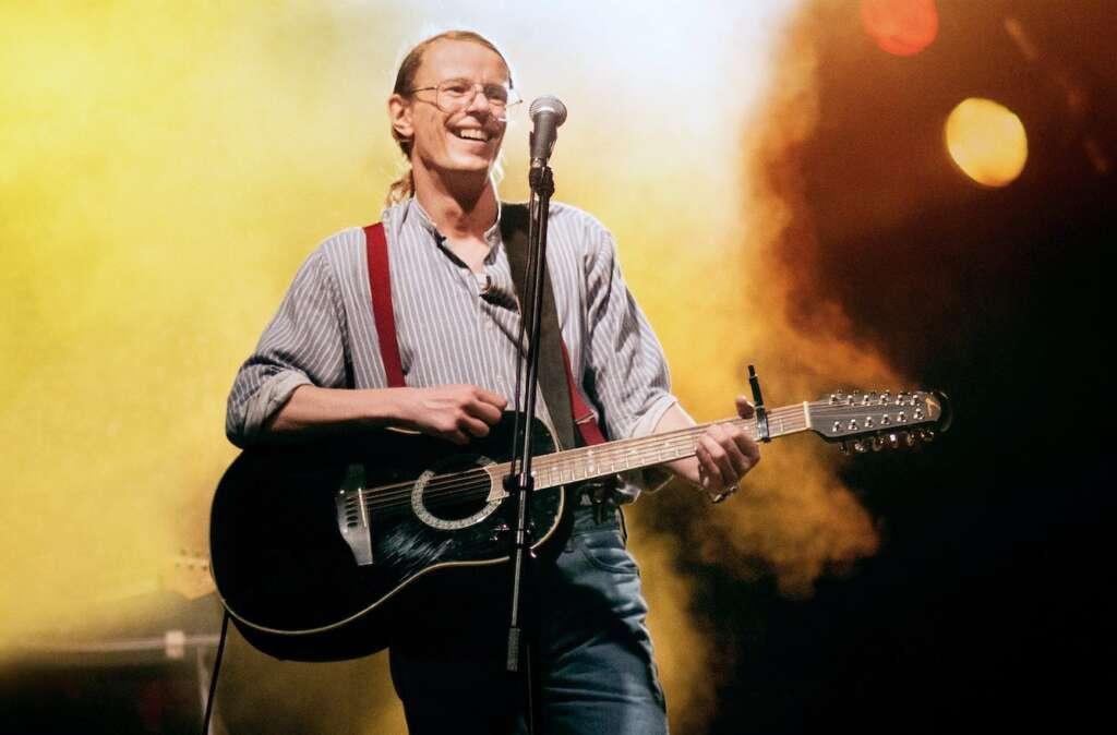 Gundermann (Alexander Scheer) mit Gitarre auf der Bühne.