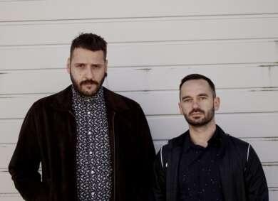 Zwei Männer stehen vor einer weißen Backsteinwand.